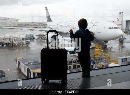 A young boy looking out of an airport window at the planes - Stock Photo