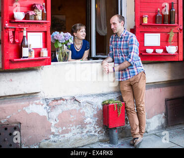 Happy young couple. A young woman looks out from the window of the house, and the man standing on the street talking - Stock Photo