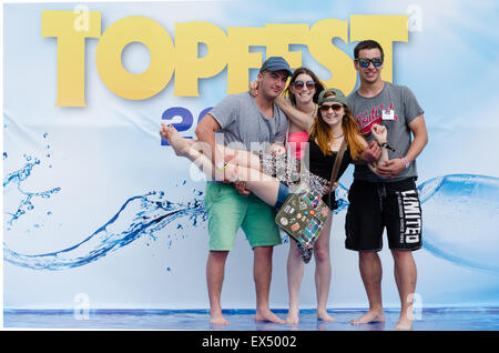 PIESTANY, SLOVAKIA - JUNE 27 2015: Visitors of Slovak music festival Topfest pose in front of sponsor's banner in - Stock Photo