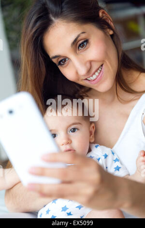 Portrait of beautiful mother and baby taking a selfie at home. - Stock Photo