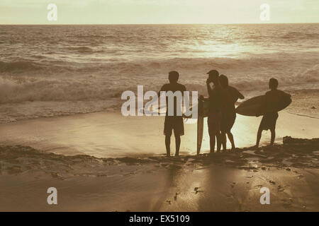 Back view of Surfers Standing on Beach