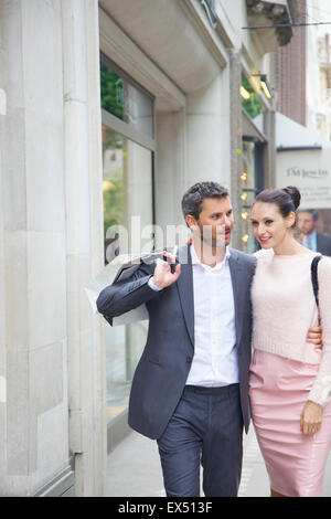 Couple Walking on City Street with Shopping bags - Stock Photo