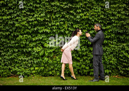 Man Videoing Woman with Camcorder in front of Green Leafy Hedge - Stock Photo