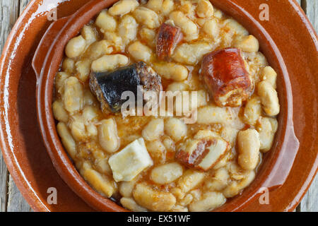 Spanish fabada in an earthenware dish and wooden background - Stock Photo