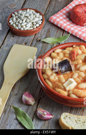 Spanish fabada in an earthenware dish on wooden table with ingredients - Stock Photo