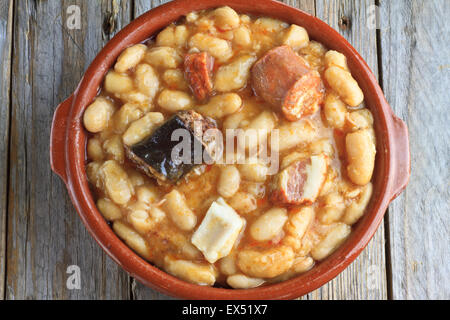 Spanish fabada in an earthenware dish on wooden table - Stock Photo