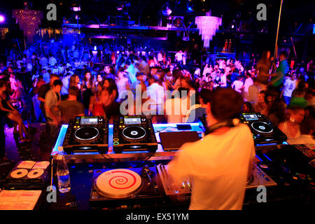 DJ on the decks / audio mixing devices and dancing clubbers. Athens nightclub, Greece. - Stock Photo