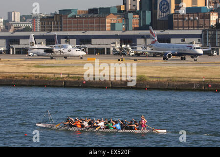 LONDON CITY DOCKLANDS AIRPORT WITH ROWING BOAT ON WATER - Stock Photo