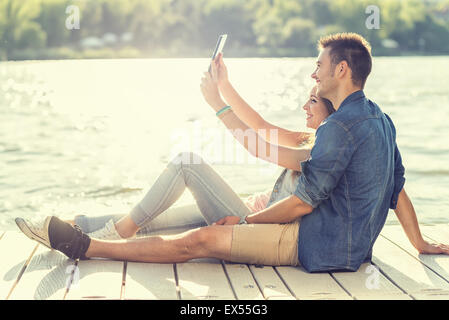 Couple in love sitting on the pier, selfie