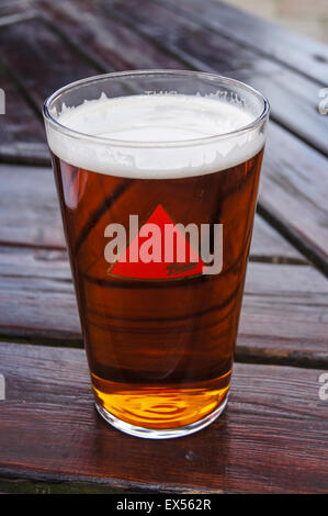 A pint of draught Bass real ale on a pub table pub table drinks glasses - Stock Photo