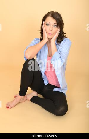 Attractive Young Woman Sitting on the Floor Wearing a Blue Shirt and Black Leggings Pulling Silly Facial Expressions - Stock Photo