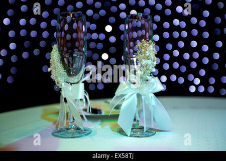 Wedding champaign glasses with lace and bow, tabletop arrangement and Lit out of focus bokeh in background. - Stock Photo