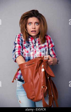 Confused woman searching something in her bag over gray background and looking at camera - Stock Photo