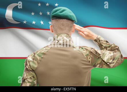 Soldier in hat facing national flag series - Uzbekistan - Stock Photo