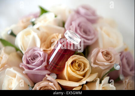 Bridal bouquets laid out before the wedding ceremony with the perfume bottle - Stock Photo