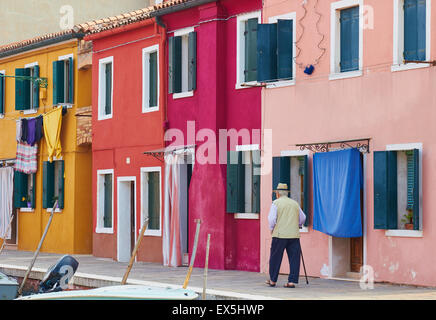 Elderly man walking past colourful row of houses Burano Venetian Lagoon Veneto Italy Europe - Stock Photo