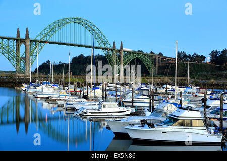 Boats moored in Port of Newport Marina and Yaquina Bay Bridge, Newport, Oregon USA - Stock Photo