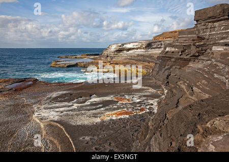 Eroded sandstone rock formations covered with algae along the barren rocky coast on the island São Nicolau, Cape - Stock Photo