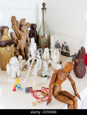 Artists wooden mannequin surrounded by small sculpted figurines - Stock Photo