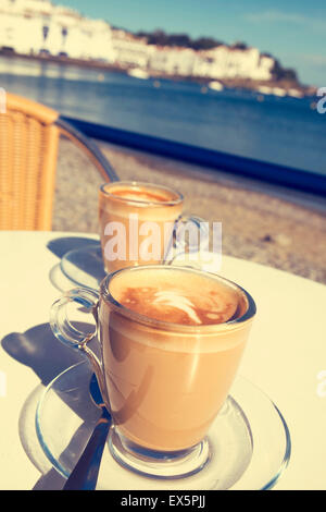 closeup of two glasses with caffe macchiato on a table in the terrace of a cafe in the seafront of Cadaques, in - Stock Photo