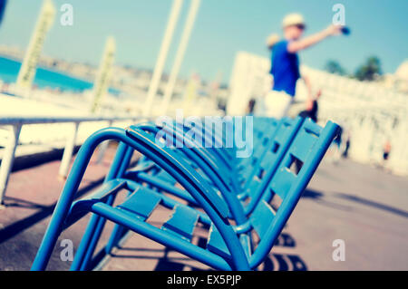 view of the characteristic blue chairs facing the Mediterranean sea at the Promenade des Anglais in Nice, France, - Stock Photo