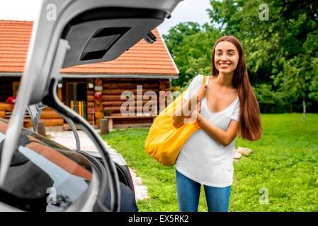 Woman packing near the car with house on backgraound - Stock Photo