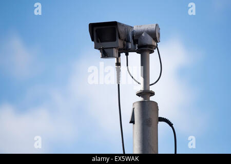 A CCTV camera with a blue sky behind. - Stock Photo