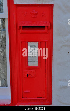 Old red VR Victorian post box set in post office shop wall - Stock Photo