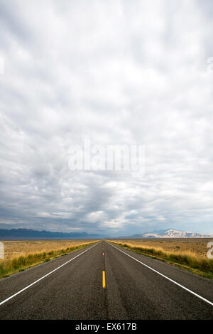 Empty open road with cloudy sky photographed from a low angle with a wide lens - Stock Photo