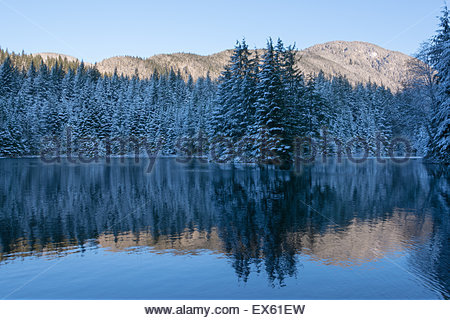 An enchanting early morning view of a forest, snow dusted fir trees and mountain tops reflected in calm blue lake - Stock Photo