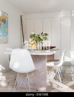 White plastic Eames chairs around custom made table of lime and waxed oak - Stock Photo