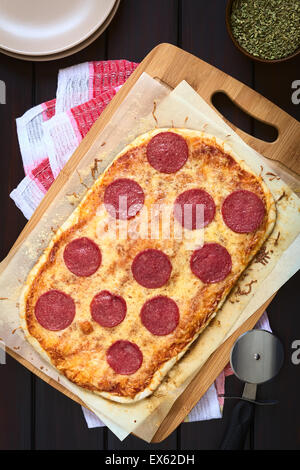 Homemade pepperoni or salami pizza on baking paper on wooden board with plates, dried oregano and pizza cutter on - Stock Photo