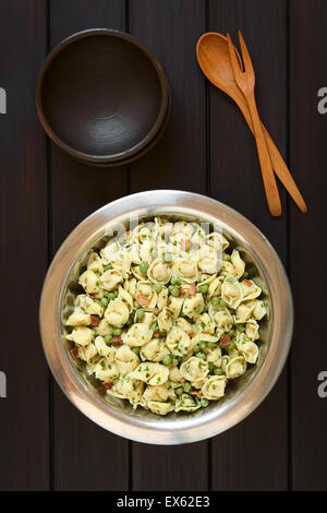 Tortellini salad with green peas, fried bacon and parsley in big salad bowl, with two small rustic bowls, wooden - Stock Photo
