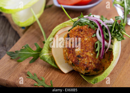Vegan burgers with quinoa and vegetables served with arugula and salad - Stock Photo