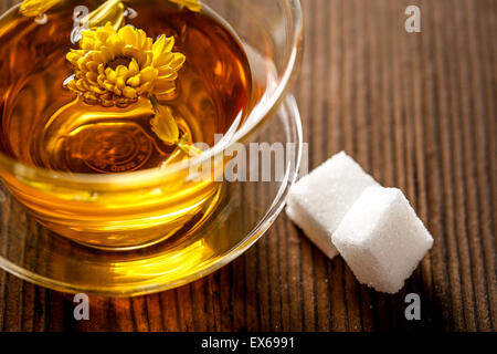 Herbal tea in a glass cup with saucer - Stock Photo