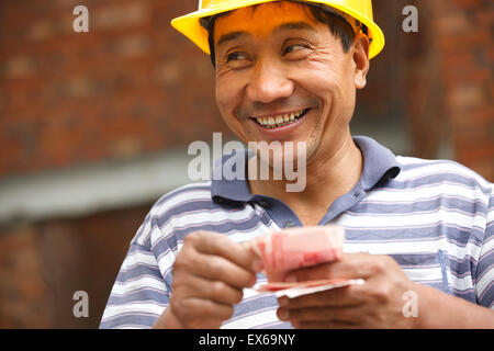 Construction worker counting paper money - Stock Photo
