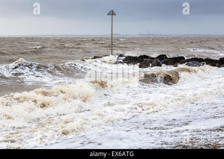 Rough sea and waves breaking over rocks in stormy bad weather under a leaden grey sky in Lee On Solent, Hampshire, - Stock Photo
