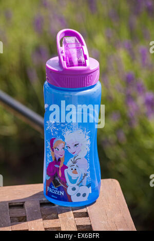 Child's drink bottle with characters from Disney Frozen on table - Stock Photo