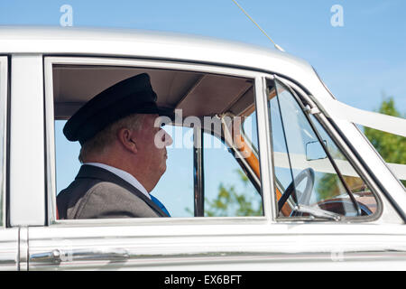 Chauffeur driving wedding car, stopped alongside at traffic lights in July - Stock Photo