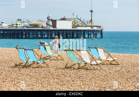 Traditional old-fashioned, empty, blue and white striped deckchairs on the beach, with Palace Pier, Brighton, East - Stock Photo