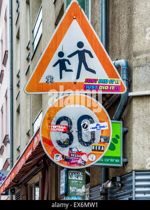 Traffic signs children crossing and speed limit defaced sticker covered berlin germany