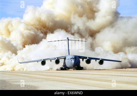 Clouds of dust behind US Air Force C-17 Globemaster III at Fort Irwin, California USA 1999 - Stock Photo