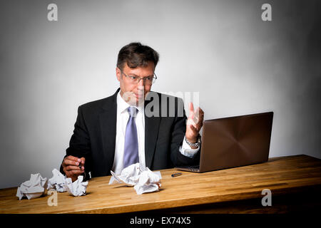 Overworked businessman with lot of files on his desk