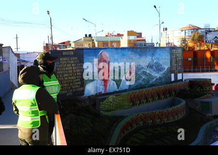 El Alto, Bolivia, 8th July 2015. Policemen patrol the footbridge next to a mural of Pope Francis in La Ceja that - Stock Photo