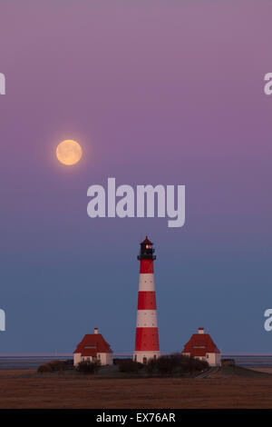 Lighthouse Westerheversand at sunset with full moon at Westerhever, Wadden Sea National Park, North Frisia, Germany - Stock Photo