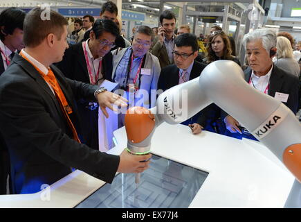 Yekaterinburg, Russia. 8th July, 2015. Foreign guests gather at the stand of KUKA industrial robots, at the Innoprom - Stock Photo