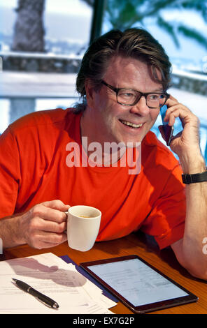 Smiling mature man using his iPhone 6 smartphone and iPad air tablet computer in luxury villa hotel pool at dusk - Stock Photo