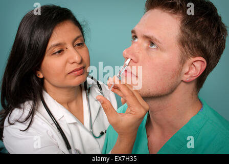 Healthcare worker administering an intranasal influenza vaccine in a patient's nostril. - Stock Photo