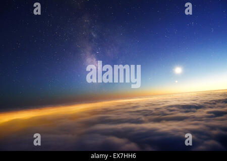 Milky Way and the Moon above night clouds. - Stock Photo