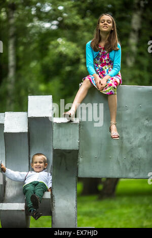 Little boy with his older sister on the Playground in the Park. - Stock Photo